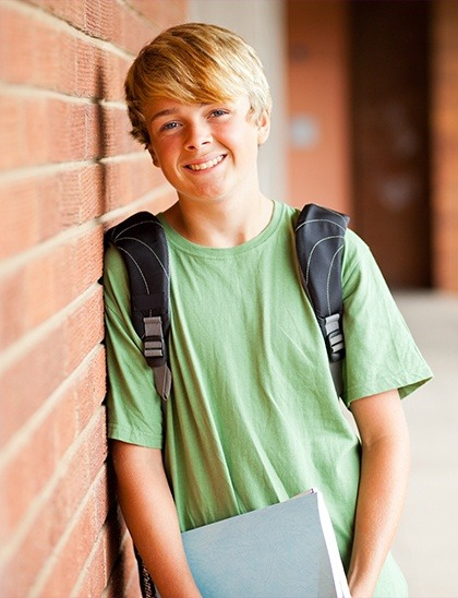 boy smiling with backpack on