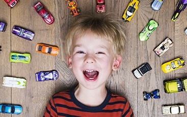 young boy laying down with cars around him