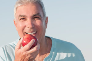 senior man eating an apple