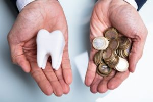 person holding money in one hand and a tooth in the other