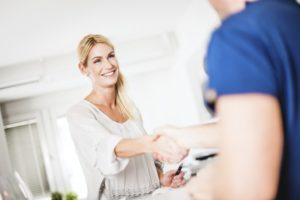 A woman shaking hands with a dental employee.